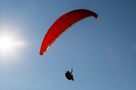 uplift: Single paraglider hovering in the sky on a sunny day. Stock Photo