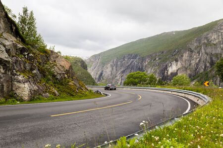 hardanger: Car driving on the Riksvei 7 public road crossing the large Hardangervidda plateau in Western Norway.