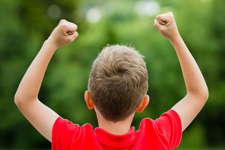 Self confident boy with raised fists celebrating a recent success or victory.