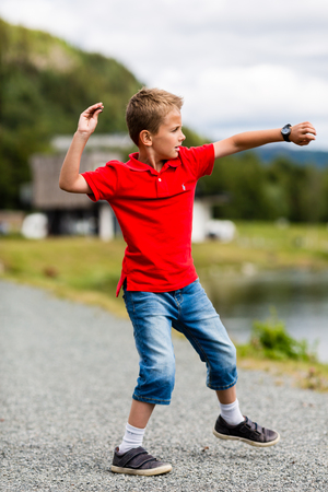 Boy throwing stone in the river on a sunny summer day in Norway.