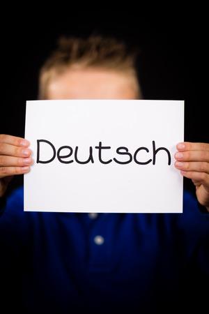 deutsch: Studio shot of child holding a sign with German word Deutsch - German in English