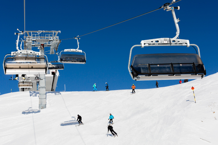 skiers: The ski resort Soelden in the Alps with chair lift and ski slope with descending skiers. Stock Photo