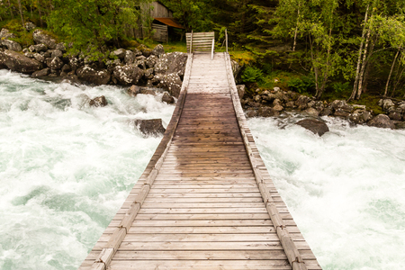 hand rails: Small wooden without hand rails spans across raging wild river near Hardangerfjord in Western Norway. Stock Photo