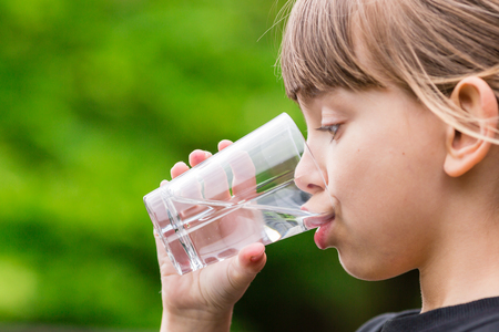 Close-up of young scandinavian child drinking fresh and pure tap water from glass with a blurred green background. Stockfoto