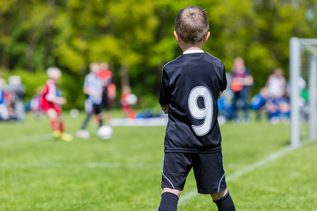 junior soccer: Young boy watching his team mates play a kids soccer match on soccer field with green grass.