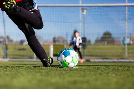 Close-up of young soccer player taking a penalty kick against a young blurred boy acting as goalie in the goal.