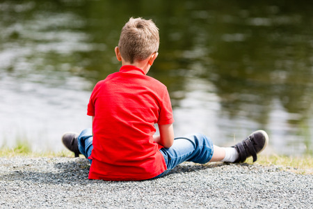 lonely boy: Lonely boy sitting by himself and thinking about life near a small lake on a summer day. Stock Photo