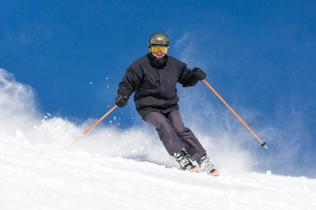 off piste: Male skier skiing in fresh snow on ski slope on a sunny winter day at the ski resort Soelden in Austria.