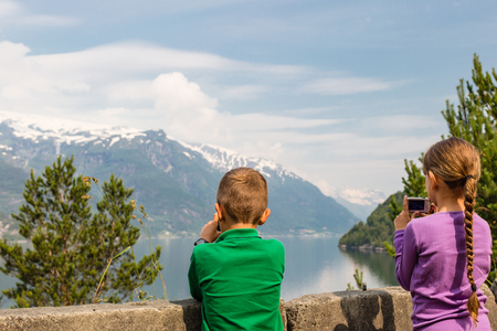 hardangerfjord: Young kids in Norway taking pictures of the surrounding scenery with their compact digital cameras. Stock Photo