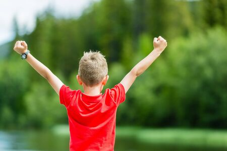 clenched fist: Young boy raising his hands in the air and celebrating success or victory.
