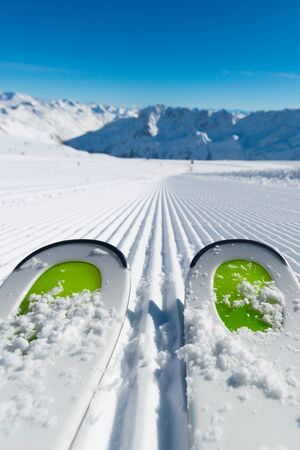 Paire de nouveaux skis debout sur la neige fraîche sur les pistes de ski nouvellement soigné à la station de ski sur une journée d'hiver ensoleillée. Banque d'images