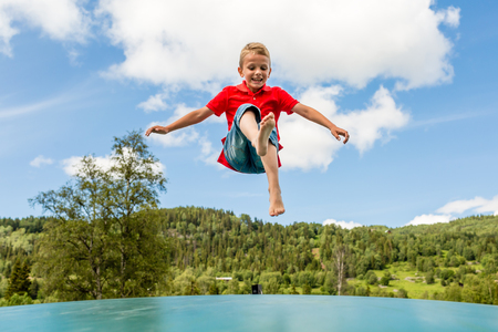 Young Scandinavian boy playing and having fun while jumping up and down on inflatable bouncing trampoline.