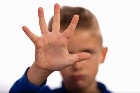 maltrato infantil: Muchacho joven que hace gesto de la parada con su mano. El foco está en la mano. La cara del niño se vuelve borrosa.