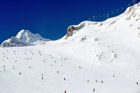 skiers: Scattered groups of skiers descend a wide ski run at the Tiefenbach glacier at the Austrian ski resort Soelden. Stock Photo