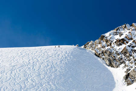off track: Tracks of off piste skiers in fresh white powder snow on a  sunny day. Stock Photo