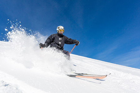 Male skier skiing in fresh snow on ski slope on a sunny winter day at the ski resort Soelden in Austria.