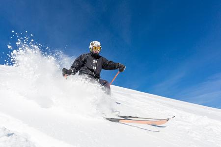 Mannelijke skiër skiën in de verse sneeuw op de piste op een zonnige winterse dag in het skigebied Sölden in Oostenrijk.