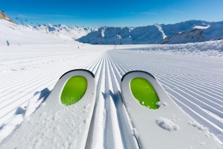 맑은 겨울 날에 스키 리조트에서 새로 손질 한 스키 슬로프에 신선한 눈에 서 새로운 스키의 쌍입니다.