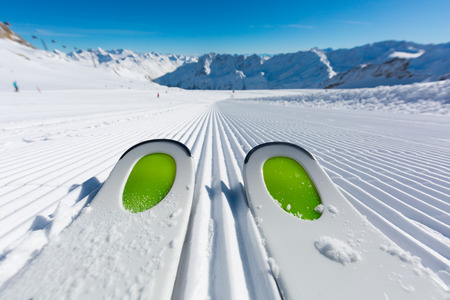 Pair of new skis standing on the fresh snow on newly groomed ski slope at ski resort on a sunny winter day. Stockfoto