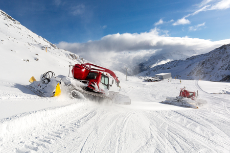 snow grooming machine: Piste basher preparing and grooming ski slope at ski resort in the Austrian Alps. Stock Photo