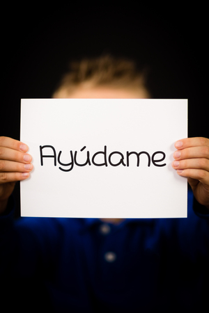 help me: Studio shot of child holding a sign with Spanish word Ayudame - Help Me
