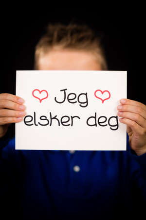 first love: Studio shot of child holding a sign with Norwegian words Jeg Elsker Dig - I Love You