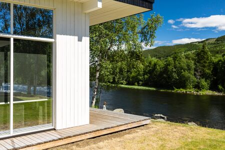 holiday home: Modern white wooden holiday home in nordic style photographed on a sunny summer day.