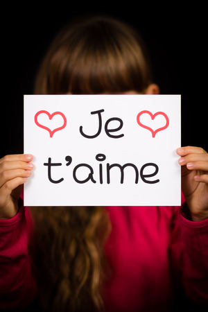 i t: Studio shot of child holding a sign with French word Je T aime - I Love You Stock Photo