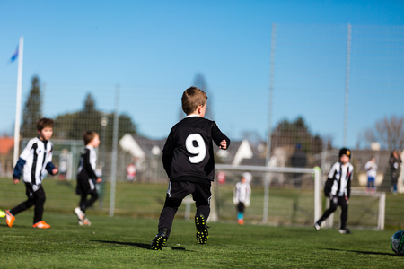youth: Young boy and his youth team during a kids soccer match outdoors on green soccer pitch. Stock Photo