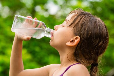 pure water: Closeup of young child drinking pure tap water from transparent plastic drinking bottle while outdoors on a hot summer day. Stock Photo