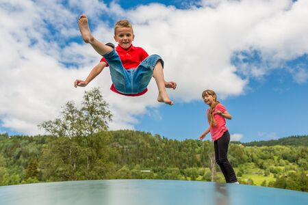 Two scandinavian children playing and having fun while jumping on large inflatable bouncing trampoline.