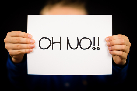 oh: Studio shot of child holding an Oh No sign made of white paper with handwriting. Stock Photo