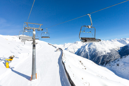chair on the lift: Chair lift hovering above the ski slopes at the Austrian ski resort Soelden.