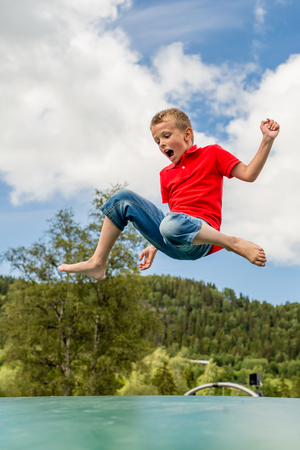 jump: Young Scandinavian boy playing and having fun while jumping up and down on inflatable bouncing pillow.