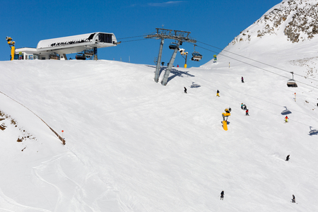 skiers: Ski slope with chair lift and skiers on a sunny winter day in a ski resort in the Alps.