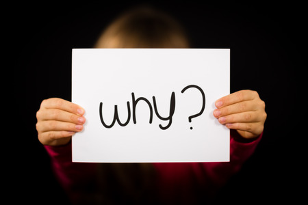Studio shot of child holding a Why sign made of white paper with handwriting. Stock Photo