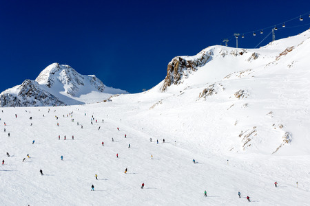 descend: Scattered groups of skiers descend a wide ski run at the Tiefenbach glacier at the Austrian ski resort Soelden. Stock Photo