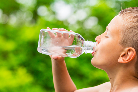 hot summer: Closeup of young boy drinking pure tap water from transparent plastic drinking bottle while outdoors on a hot summer day.