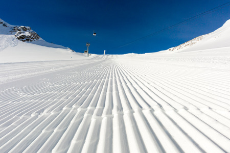 ski run: Fresh snow at recently groomed ski run at ski resort in the Alps on a sunny winter day. Stock Photo