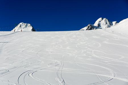 Verse ski tracks op skipiste met nieuwe witte sneeuw in het skigebied Sölden in de Oostenrijkse Alpen. Stockfoto