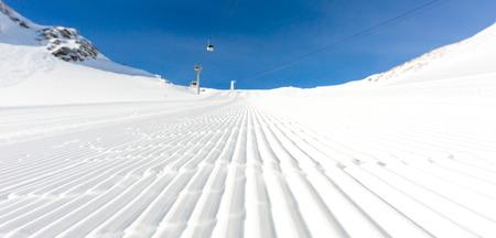 skipiste: Fresh snow at recently groomed ski run at ski resort in the Alps on a sunny winter day. Lizenzfreie Bilder