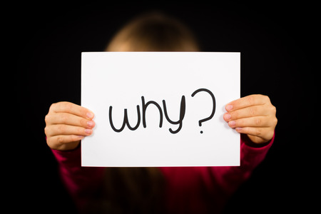 why: Studio shot of child holding a Why sign made of white paper with handwriting. Stock Photo