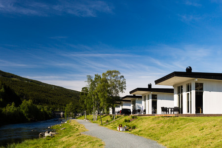 Modern white wooden holiday home in nordic style photographed on a sunny summer day.