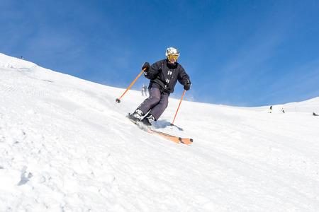 Férfi síelő síelés a friss hóban a sípályán, egy napsütéses téli napon a sípálya Soelden Ausztriában.