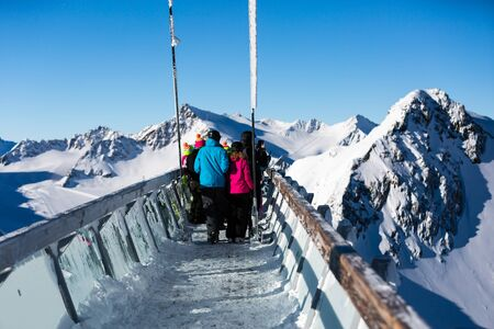 skiers: Skiers at the Austrian ski resort Soelden take a break at the panoramic skywalk at the top of the Tiefenbachkogl mountain. Stock Photo