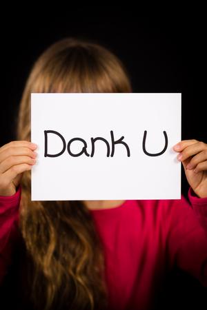dutch girl: Studio shot of child holding a sign with Dutch words Dank U - Thank You Stock Photo