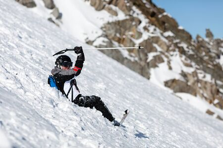 skiing accident: Male skier skiing in fresh snow on ski slope on a sunny winter day at the ski resort Soelden in Austria.