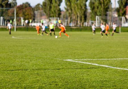 sports venue: Shallow depth of field shot of group of male soccer players playing amateur soccer match on sunny summer day on simple sports venue in Denmark.