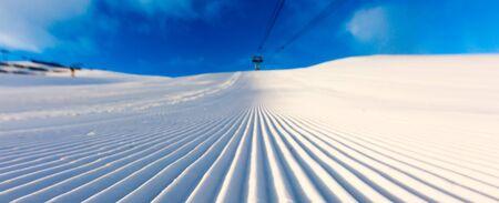 ski run: Newly groomed snow on ski piste at ski resort on a sunny winter day.