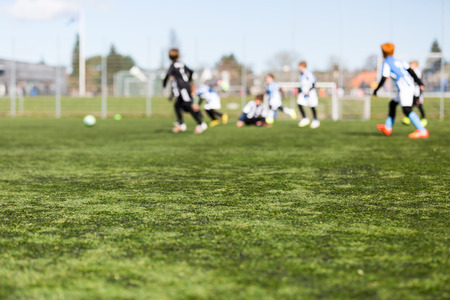 soccer pitch: Blur of young kids playing a youth soccer match outdoors on an green soccer pitch. Stock Photo